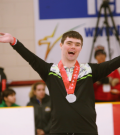"""Jordan Koughan lifts his arms up in victory with a big smile on the podium"""