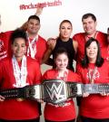 Athletes stand for a photo with WWE star Becky Lynch