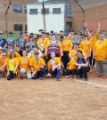 A group of two softball teams pose for a team photo on a baseball diamond
