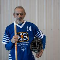 Richard Myette poses with his floor hockey stick looking into the camera