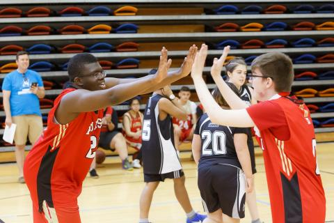Athletes high five at a ASAA Unified sport event