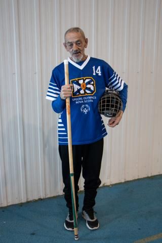 Richard Myette poses with his floor hockey stick and in his jersey, looking at the camera.