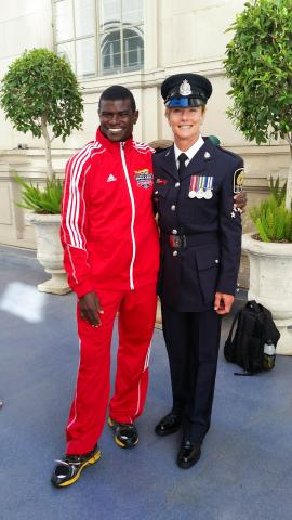 Inspector Joanne Wild, dressed in her police uniform poses for a photo with Special Olympics BC athlete Nigel.