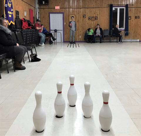Logan stands at the end of the makeshift bowling alley at the community hall.